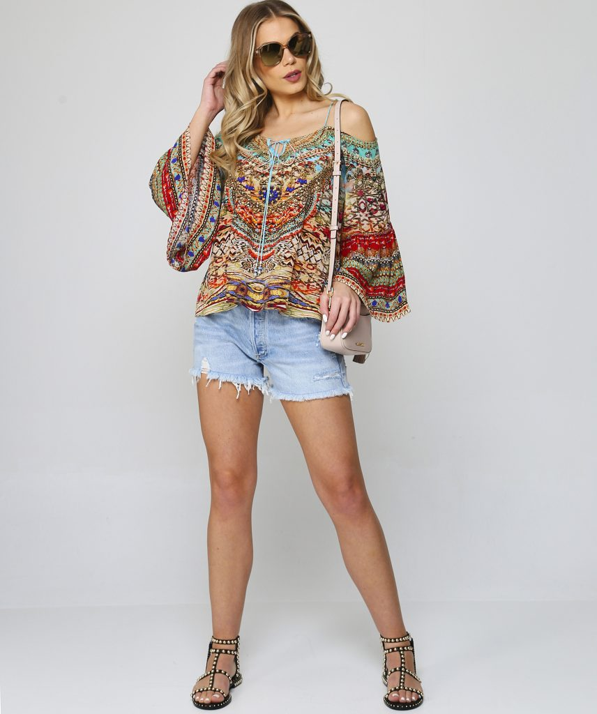 This is an image of a woman with long blonde hair posing in a long sleeves top, denim shorts and sandals. She is carrying a shoulder bag and wearing sunglasses.