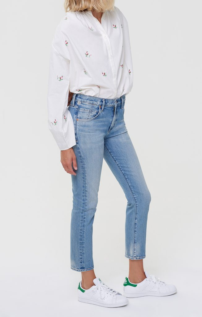 This is an image of a woman wearing a blouse and blue jeans in a mid-rise, slim-fit, cropped silhouette.
