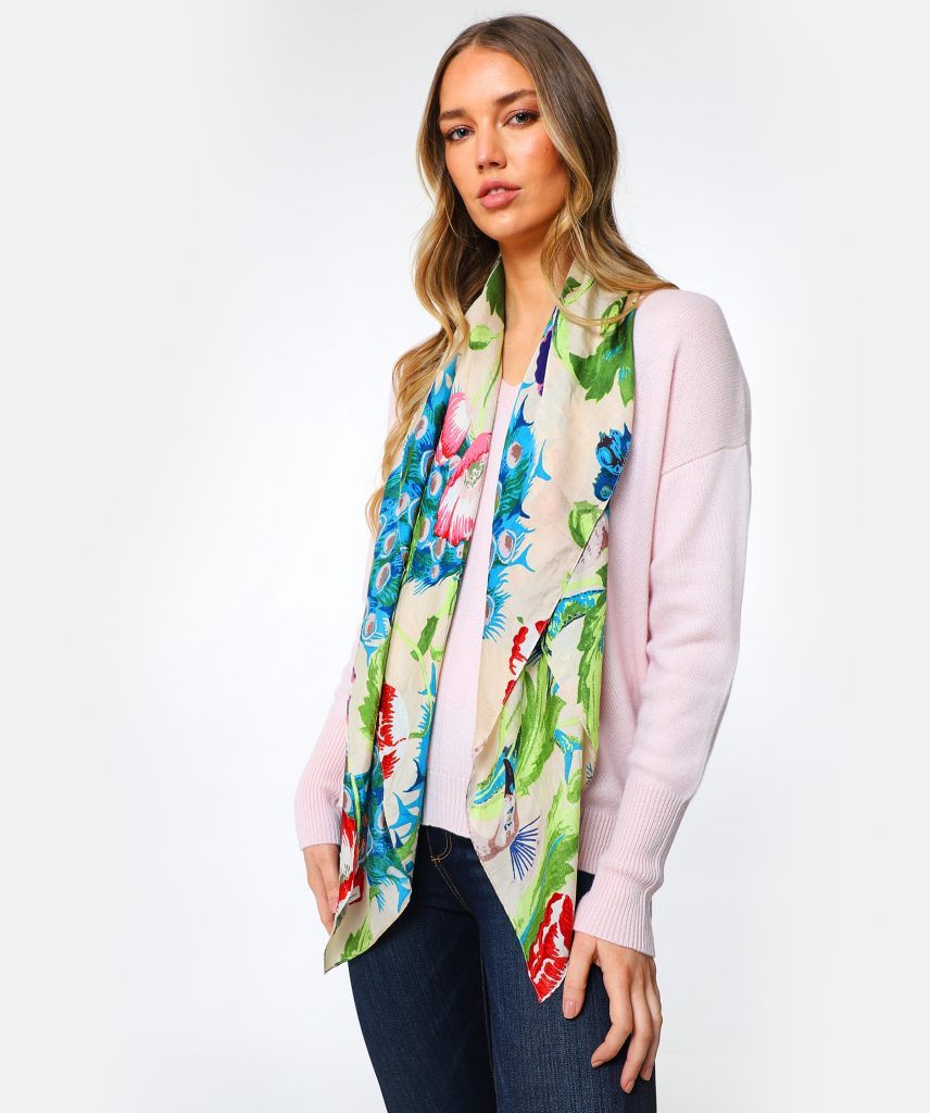 This is an image of a woman with blonde hair wearing a pink jumper, blue jeans and a bright patterned scarf