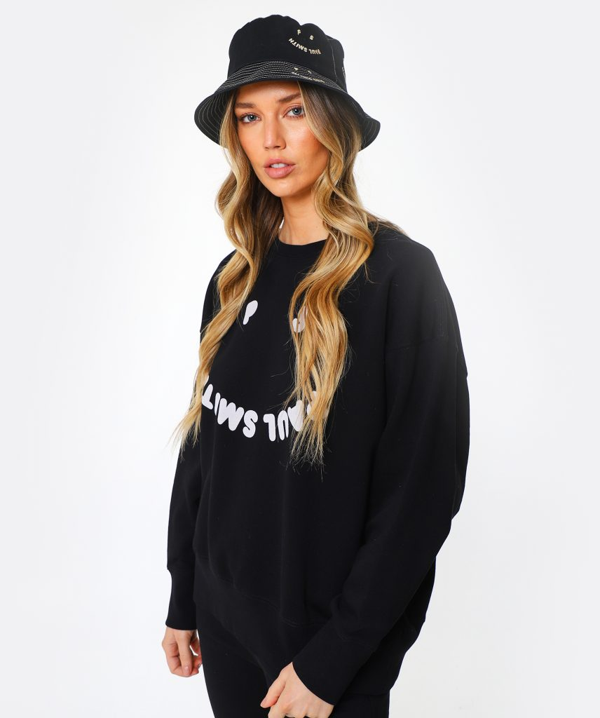 This is an image of a blonde woman wearing a black sweatshirt, black trousers and a black bucket hat