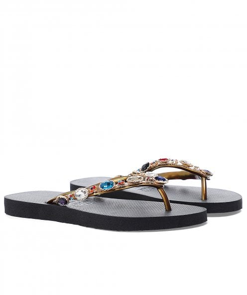 This is an image of a pair of black flip flops with gold straps and crystal embellishment